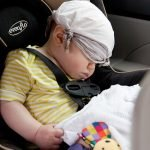 baby asleep in a car seat with a rag covering their eyes